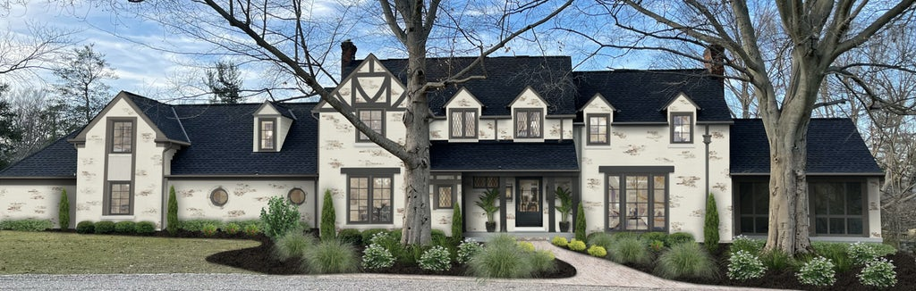 two story large stone traditional french country home with limewash and black roof