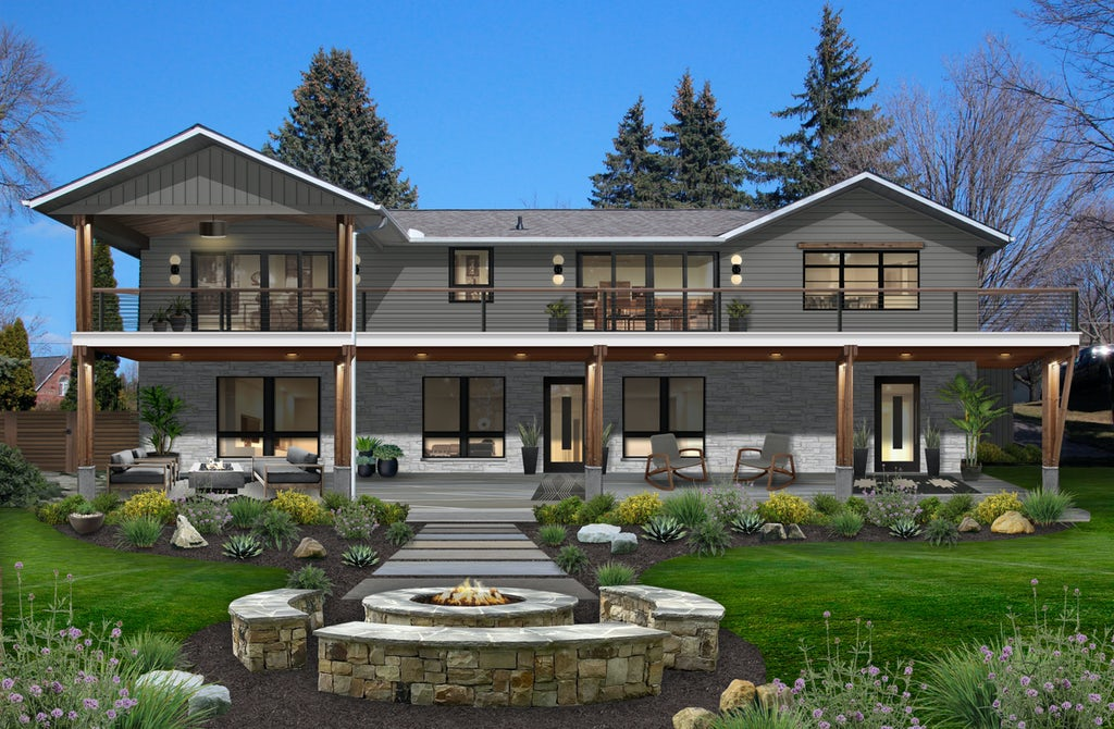 After photo of a large two-story home that has been redone in James Hardie siding in the color Aged Pewter on the top level, and stone on the first floor. The rustic home has a long walkway that leads out to a stone fire pit with seating, as well as a grassy yard and plentiful landscaping.