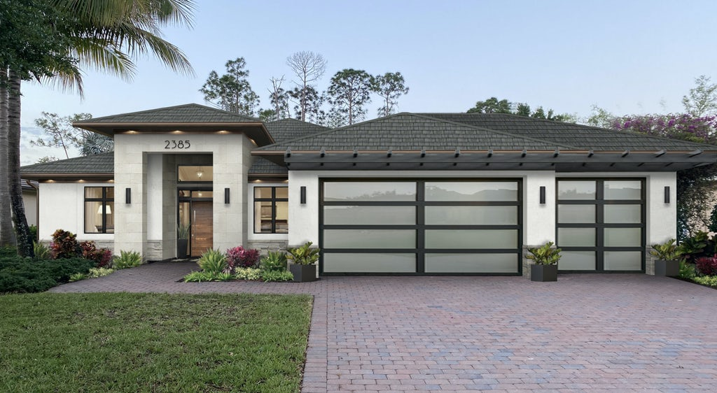 small ranch spanish style home with low pitch roof and glass paneled garage doors