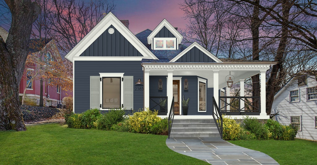 An updated exterior home design for an historic cottage featuring siding painted in Haley Navy, white trim and accents, and shutters painted in Willow Creek.