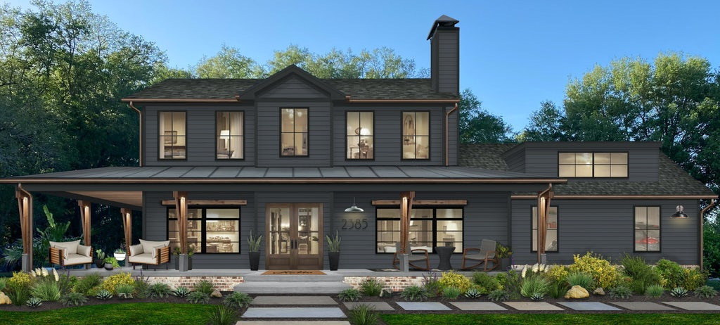 large transitional two story home painted in dark blue gray with a large wraparound porch