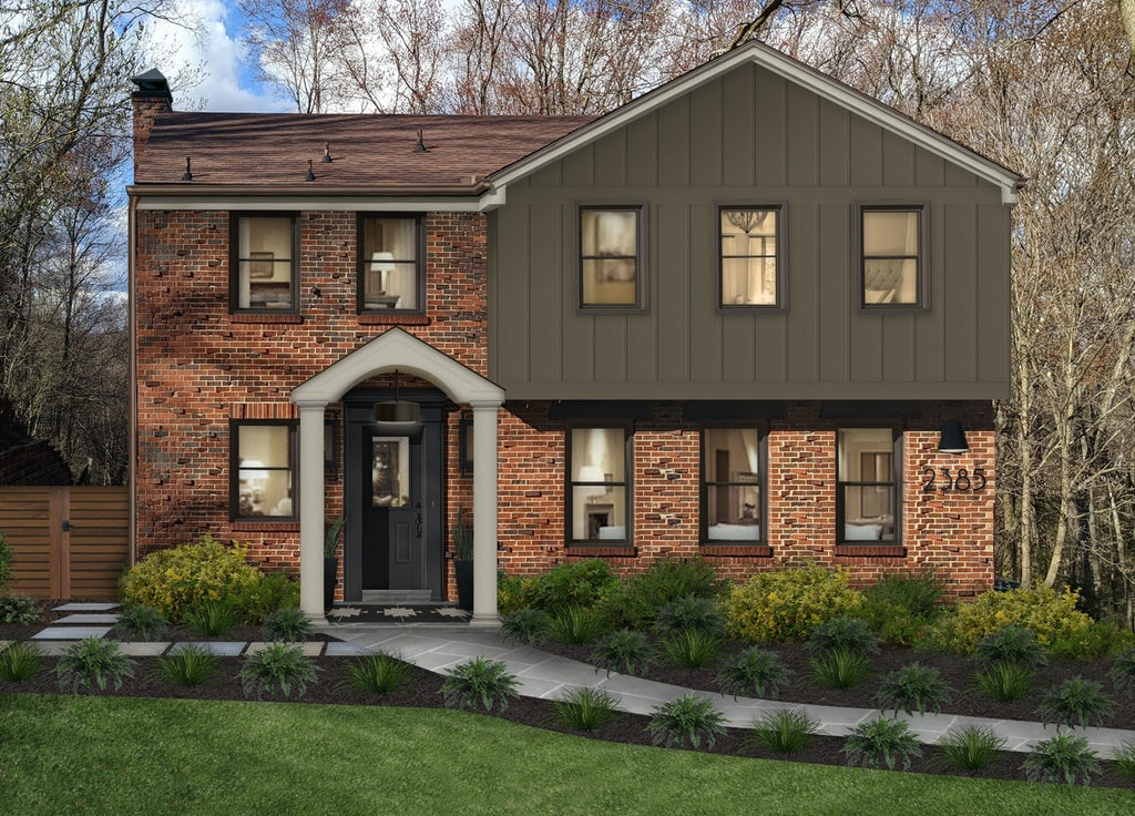 A brick home which is partially painted with James Hardie Hardie Board siding color Timber Bark, a deep green color. The home has a beautiful front walkway with stunning landscaping, and a covered front entry.