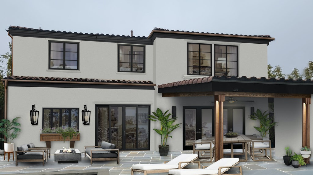 backyard view of a spanish style two story home with multiple slider doors leading out to patio furniture