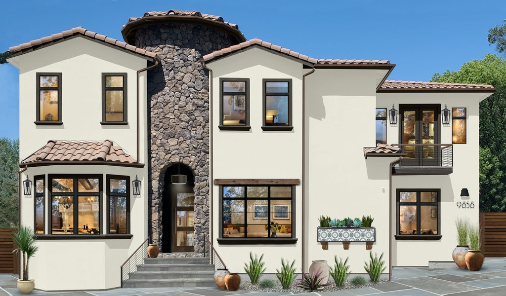 two story spanish style home with center stone turret and large black frame windows