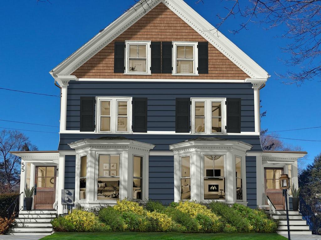 three story modern victorian house with cedar shingles, dark blue siding, and ornate white painted bay window trim